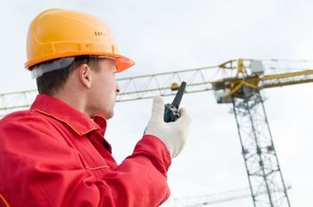 Builder operating crane with walkie talkie